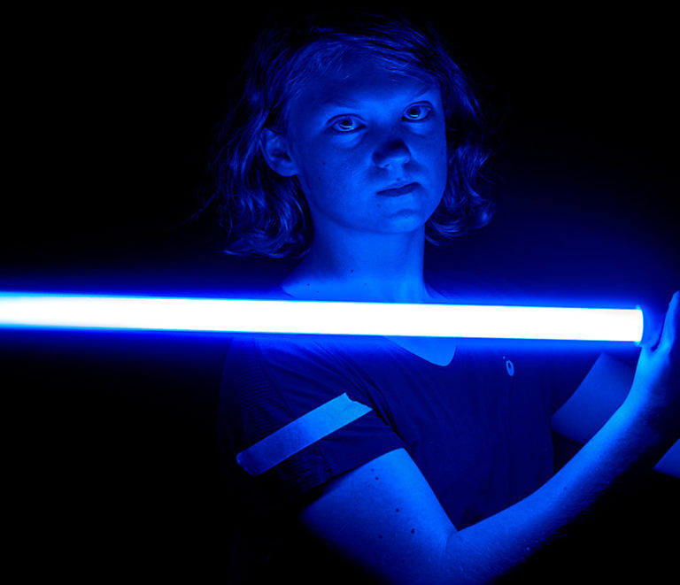 Padawan stays balanced with the light side. A blue lightsaber serves as mood lighting in a photo opp.
